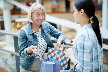 Smiling satisfied mature woman frowning forehead from excitement showing purchase in shopping bag to friend while they chatting in lobby of mall Stock Photo