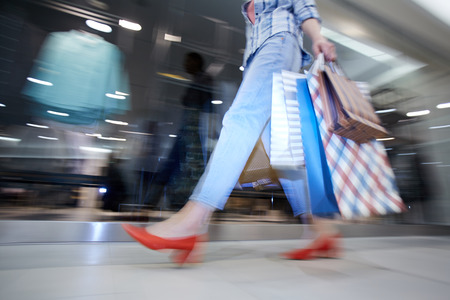 Blurred motion of lady shopaholic with paper bags in corridor of mall, unknown woman walking by shop-window
