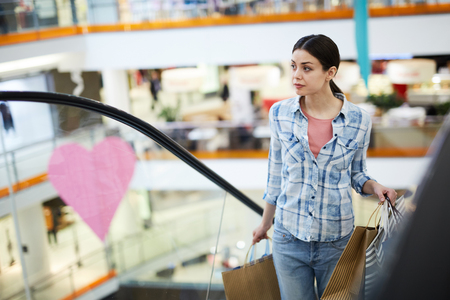 Young woman with shopping bags moving up escalator