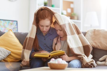 Two Sisters Reading Book Stock Photo