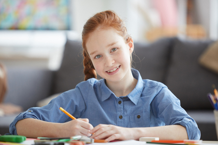 Smiling Red Haired Girl Drawing Pictures Stockfoto