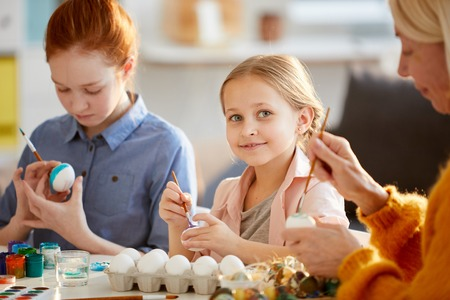 Cute Girl Painting Eggs for Easter Фото со стока
