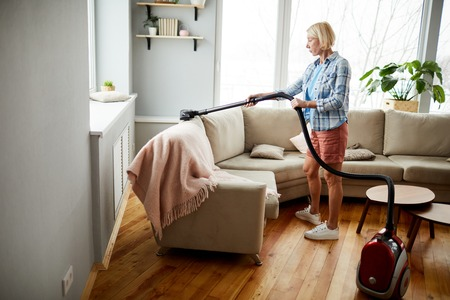 Woman using vacuum cleaner Stock Photo