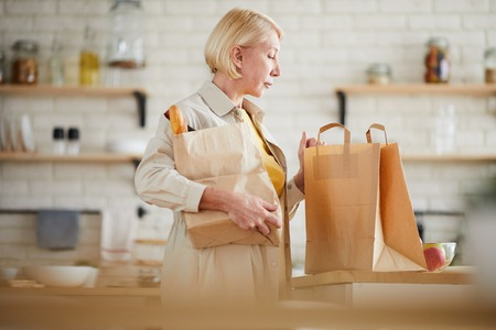 Mature woman coming home after shopping in grocery store