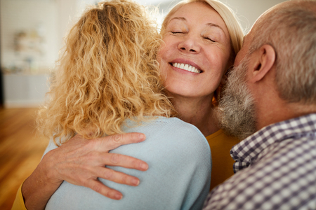 Happy mature woman embracing friends