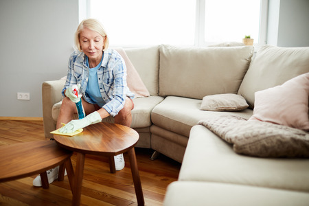 Mature woman removing dust from coffee table Foto de archivo - 119823025