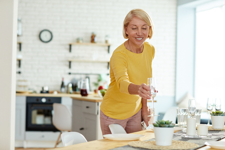 Smiling woman putting flute on table