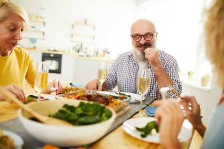 Mature man chewing vegetable leaf at dinner with friends