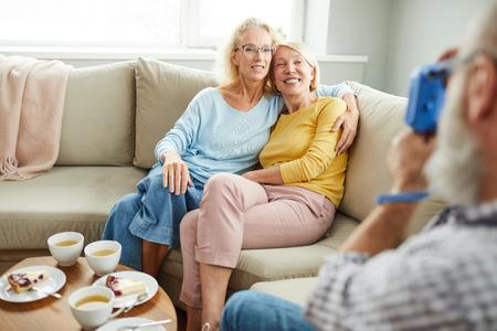 Happy ladies friends hugging on sofa