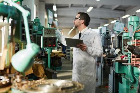 Arbeiter, der Maschinen im Werk bedient
