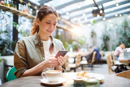 Pretty woman checking messenger in cafe Banco de Imagens