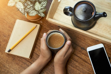 Hands of woman drinking tasty balck coffee in the morning