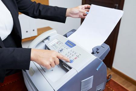 Secretaria femenina imprimiendo algún documento, gráfico o informe