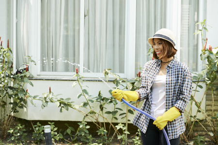 Happy woman using hose when water plants in backyard