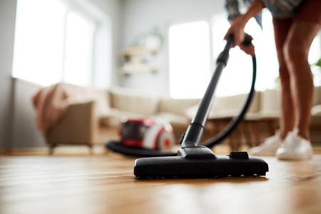 Close-up of unrecognizable woman vacuuming floor at home