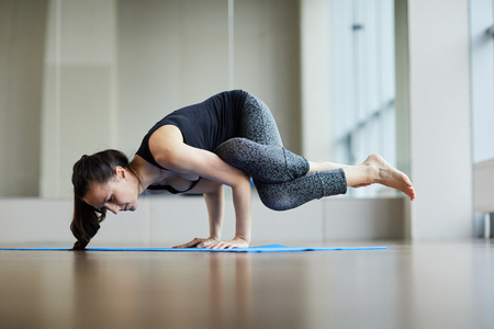 Strong woman performing eight-angle pose