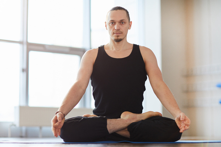 Muscled young man meditating alone