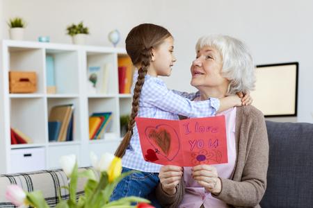 Senior Woman Embracing Cute Girl