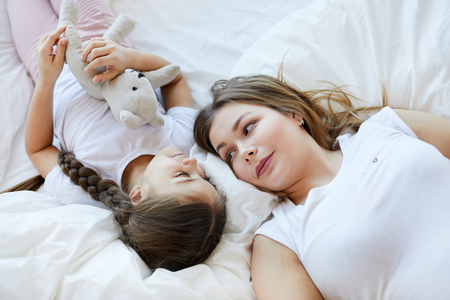 Mother and Daughter Lying on Bed Banque d'images