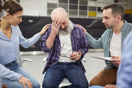 Bearded Senior Man Crying in Support Group Stock Photo