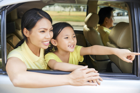 Smiling pretty Vietnamese mother and daughter enjoying view from car window Stock Photo