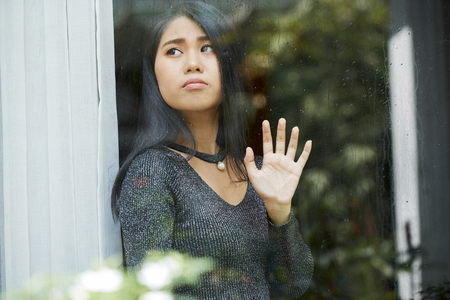 Pensive young woman looking through window