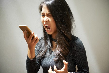 Woman shouting at smartphone Stock Photo