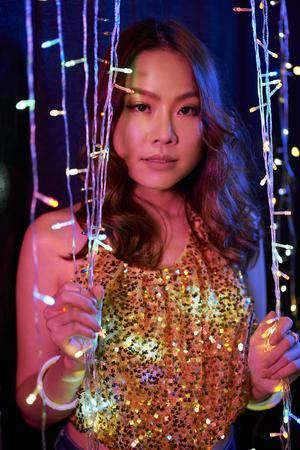 Woman standing among sparkling garland 写真素材
