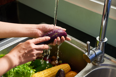 Housewife rinsing vegetables