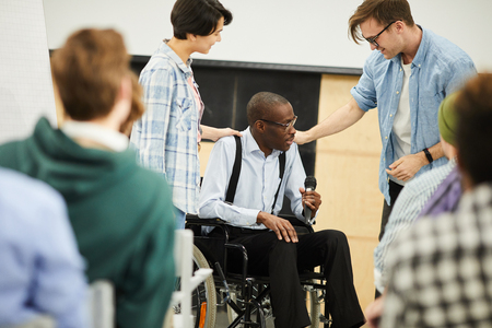 Disabled black man in wheelchair giving lecture at conference