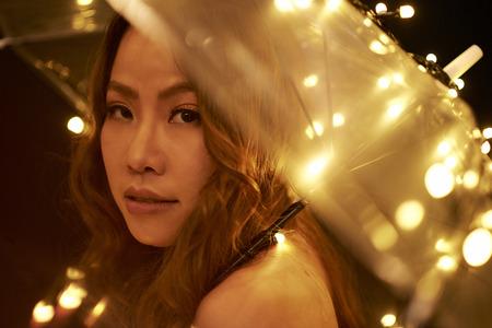 Woman posing with sparkling umbrella Stock Photo