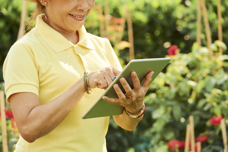 Smiling gardener with tablt computer