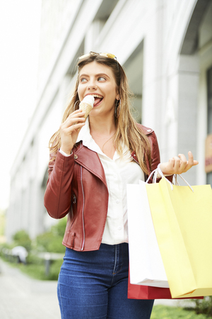 Woman eating icecream after shopping