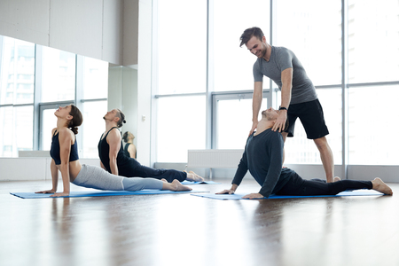 Junger Yogalehrer, der die Kobrahaltung der Schüler korrigiert
