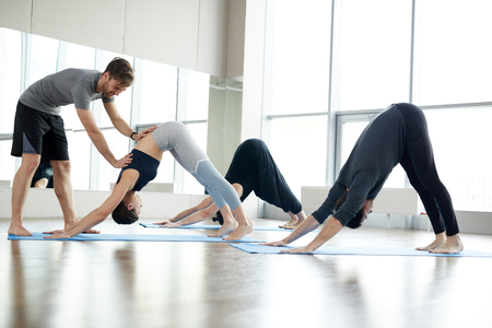 Qualified yoga coach assisting students at class