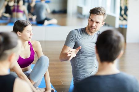 Chico deportivo compartiendo ideas en clase de yoga