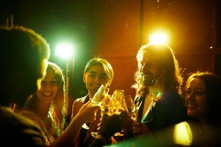 Hilarische vrienden die champagne drinken op feestje