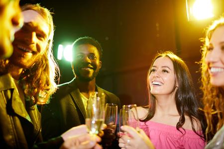 Positive friends talking in nightclub Imagens