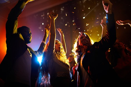 Excited people dancing at concert in nightclub