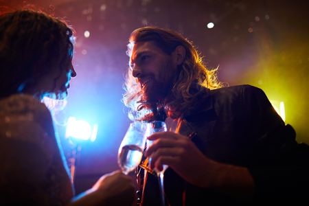 Hipster guy talking to charming lady in nightclub