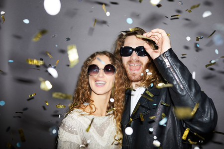 Excited couple under golden confetti