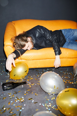 Drunk man sleeping on sofa in nightclub Reklamní fotografie