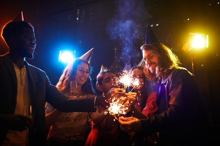 Young friends lighting sparklers at party