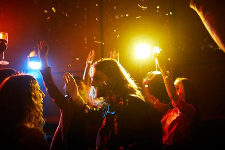 Opgewonden mensen dansen onder confetti Stockfoto