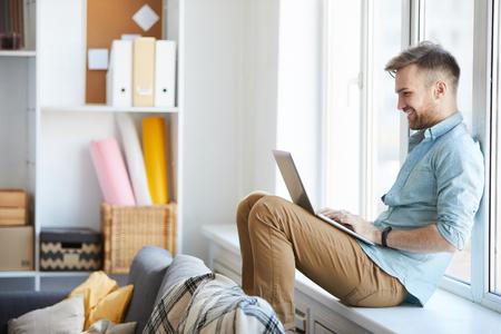 Młody mężczyzna korzystający z laptopa przez okno