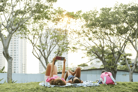 Relaxed school girls using gadget in city park
