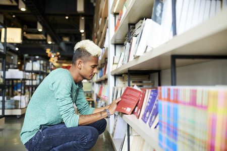 Black student reading content of book in store
