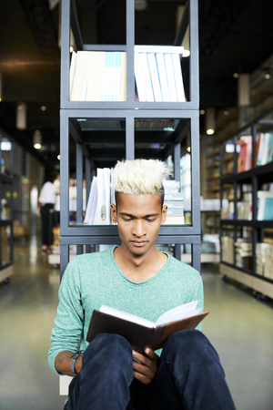 Curious black student reading book in library