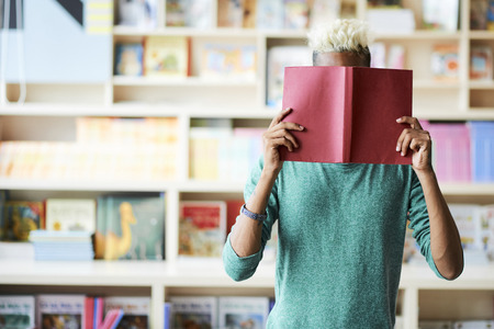Student hiding face behind book