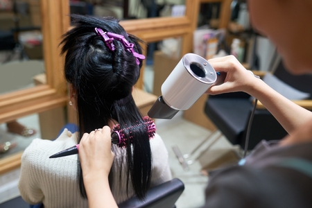 Styling hair using hair dryer Foto de archivo